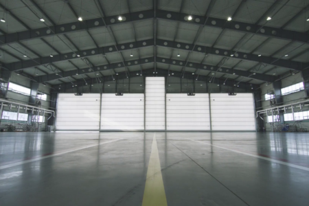 videoblocks-roller-shutter-door-and-concrete-floor-inside-factory-building-for-industrial-background-airplane-in-front-of-half-opened-door-to-hangar-the-open-door-of-the-hangar-mechanic-open